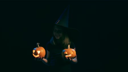 tykev : Girl wearing black witch hat holding jack-o-lanterns posing looking at camera, over black background