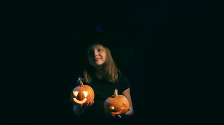 questão : Happy joyful girl wearing black witch hat holding jack-o-lanterns dancing looking out of frame, over black background Stock Footage
