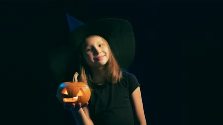 Girl wearing black witch hat holding jack-o-lantern smiling at camera and showing V hand sign, over black background