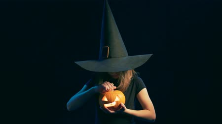 questão : Girl wearing black witch hat holding jack-o-lanterns opening a pumpking and making a scary face, over black background Stock Footage