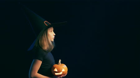 salva : Side view of a Girl wearing black witch hat holding jack-o-lantern and looking forward at blank copy space, over black background, turning to camera and smiling