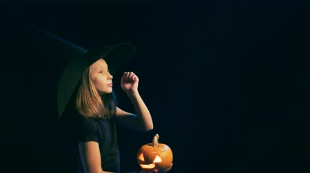 approving : Side view of a Girl wearing black witch hat holding jack-o-lantern looking forward at blank copy space and dancing, over black background, turning to camera and gesturing thumb up