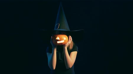 witch hat : Happy playful child girl wearing black witch hat holding jack-o-lantern in front of face posing smiling joyful, over black background
