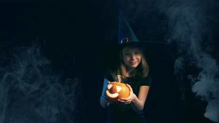 approving : Front view of a Girl wearing black witch hat holding jack-o-lantern and dancing, over black background with smoke