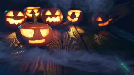 vigyorgó : Hand covering Halloween pumpkins on weathered wooden planks, with smoke on foreground, blue back light, sliding video