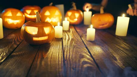 esculpida : Human hands firing candles Halloween pumpkins on weathered wooden planks, with smoke on foreground, blue back light, sliding video
