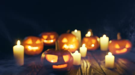vigyorgó : Defocused video of Halloween pumpkins on weathered wooden planks, with smoke on foreground, blue back light, sliding video Stock mozgókép