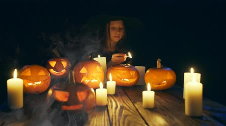 witch hat : Girl in costume of witch firing candles Halloween pumpkins on with smoke on foreground, sliding video