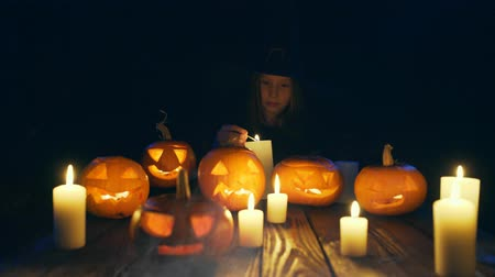 witch hat : Girl in costume of witch firing candles Halloween pumpkins on with smoke on foreground and looking at camera smiling, sliding video Stock Footage