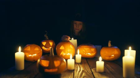 esculpida : Girl in costume of witch firing candles Halloween pumpkins on and looking at camera smiling, sliding video Vídeos