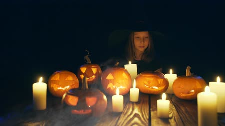 tykev : Girl in costume of witch looking at candles Halloween pumpkins on with smoke on foreground sliding video defocused at the end Dostupné videozáznamy