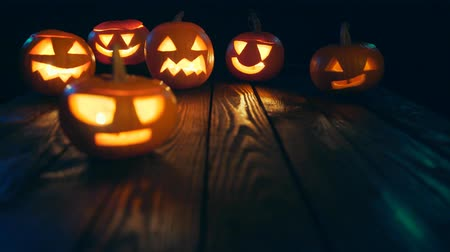 tykev : Halloween pumpkins on weathered wooden planks, no smoke, blue back light, sliding video, rack focus