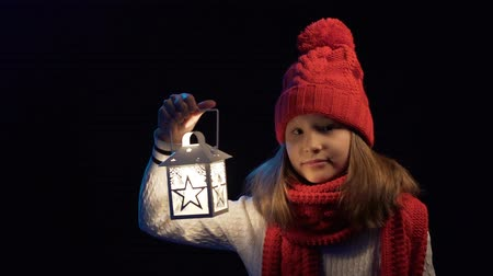 knitted : Little girl wearing knitted winter hat and scarf holding a lantern appearing in frame looking at camera smiling and waving greeting you, over black background