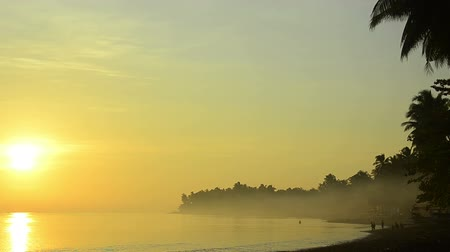 indonesia : bali cost in morning fog with children fishing at the beach
