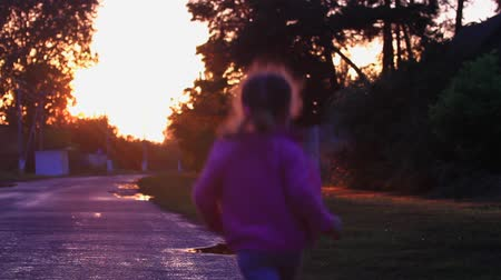 pocsolya : little girl rides through the puddles in the evening after rain Stock mozgókép