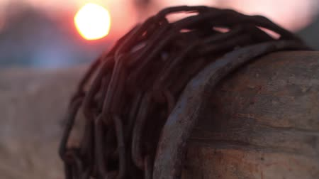 прикован : chain wrapped around a wooden beam at sunset