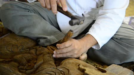 Thai man carving wood at Chiang Mai, Thailand. Close up wood carver working.