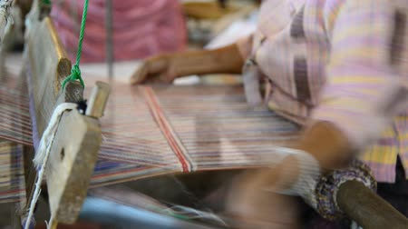 Traditional Thai textile manufacture in craft village, Old women work on wooden weaving thread machines and spin yarn creating cotton fabric. Chaing Mai, Thailand. Stok Video