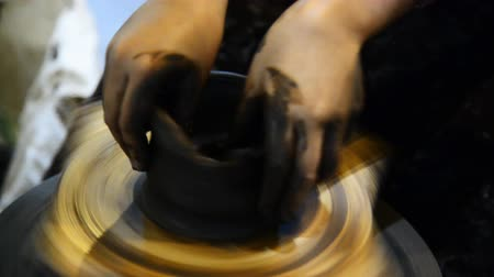 Potter teaches hands shaping the clay on the working wheel. Hands modelling the clay shaping on the working wheel.