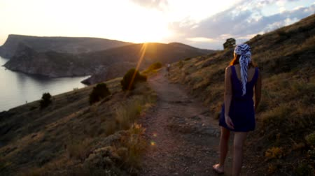 krym : girl in the headscarf goes to the sunset behind the mountain