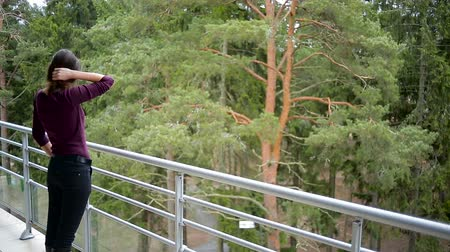 overlooks : girl in maroon sweater standing at a large balcony of the hotel which overlooks the pine forest