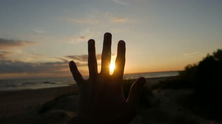 dedo : guy looks at the hand and fingers during sunset