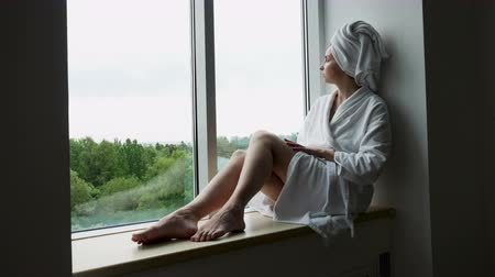melankoli : girl in a Bathrobe and towel on head sits on the window sill on the highest floor of the hotel