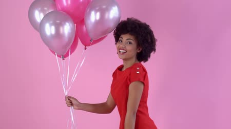 африканского происхождения : Young woman studio isolated on pink womens day holding balloons
