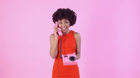 африканского происхождения : Young woman studio isolated on pink womens day in red dress talking cheerful on telephone