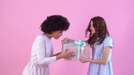 африканского происхождения : Young women studio isolated on pink womens day pulling gift box