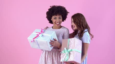африканского происхождения : Young women studio isolated on pink womens day holding presents Стоковые видеозаписи