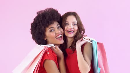 африканского происхождения : Young women studio isolated on pink womens day holding shopping bags