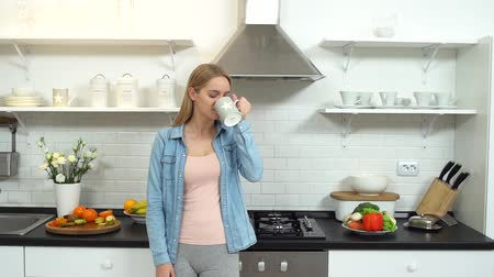 cotidiano : Young woman alone at kitchen standing drinking water Stock Footage
