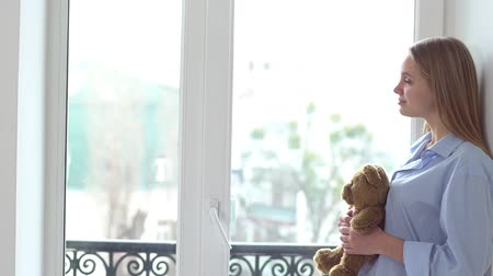 cotidiano : Young woman alone at home near window hugging teddy bear looking out
