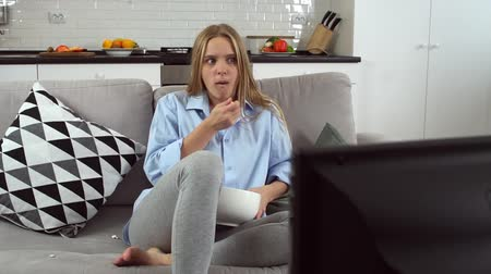 diário : Young woman alone in living room sitting watching series eating popcorn Vídeos