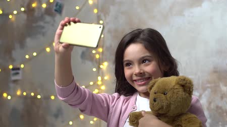 festett : Little girl alone in room hugging teddy looking at smartphone camera cheerful