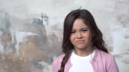 Little girl isolated on painted wall disgusted