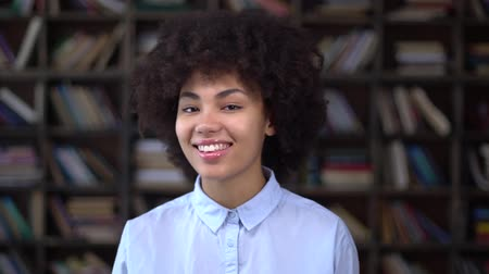 African young woman in library grimace cheerful