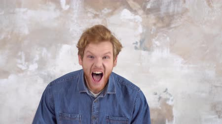 Young red-haired man isolated on painted wall shouting angry