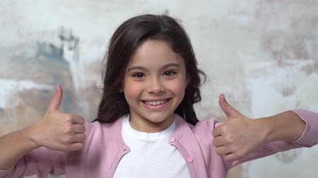 Little girl alone isolated on painted wall showing thumbs up joyful