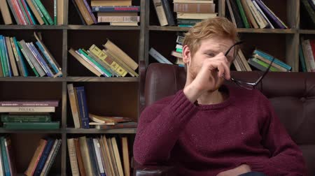 Red-haired man sitting in library putting on eyeglasses Stock mozgókép