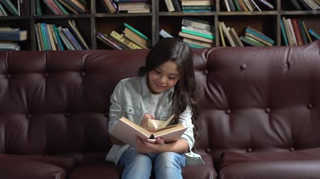 Little girl sitting in library reading book cheerful