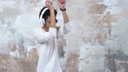 Young man alone isolated on painted wall in headphones and sunglasses dancing