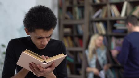 Young man in library reading book concentrated
