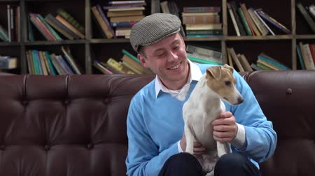 Young man in library in flat cap sitting playing with dog smiling