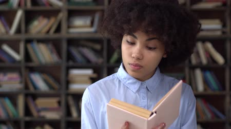 Young african woman in library reading book looking aside thoughtful Стоковые видеозаписи