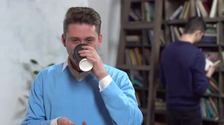 Young man in library drinking hot coffee looking camera joyful