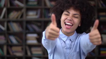African young woman in library showing thumbs up happy