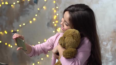 Little girl alone in room hugging teddy taking selfie pictures cheerful Stock mozgókép
