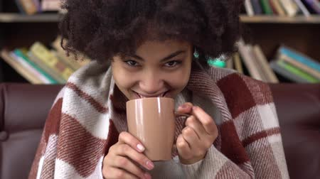Young african woman in library sitting covered with plaid drinking hot coffee joyful Стоковые видеозаписи